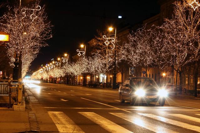 svítící auto jede noční ulicí